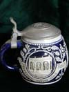 This saltglaze style stein feature a lyre musical instrument on the lid